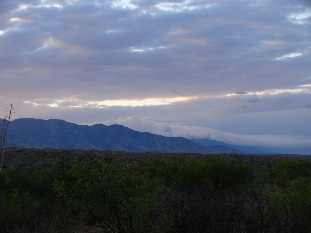Photo showing clouds rolling down mountain ridge above the flat  Aravaipa landscape at dawn